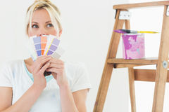 Woman holding color swatches in new house. Thoughtful young woman holding color swatches in a new house Royalty Free Stock Image