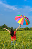 Woman holding color umbrella in yellow field Stock Photo