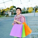 Woman holding colored paper shopping bags Stock Photo