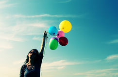 Woman holding colorful balloons Stock Photos