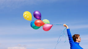 Woman holding colorful balloons Stock Images
