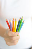 Woman holding colorful pencils in hand Royalty Free Stock Photos