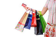 Woman holding colorful shopping bags and credit card isolated on white Stock Images