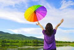 Woman holding colour umbrella against the sun sky Royalty Free Stock Photography