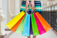 Woman holding colourful shopping bags at the mall. Royalty Free Stock Photography