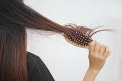 Woman holding combing with brush and clean long hair, Haircare concept stock images