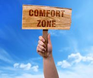 Comfort zone wooden sign. A woman holding comfort zone wooden sign on blue sky background royalty free stock photo