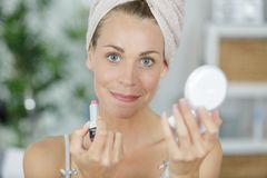 Woman holding compact mirror and applying makeup stock photography