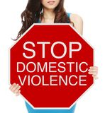 Stop Domestic Violence. A woman holding a conceptual stop sign on domestic abuse or violence royalty free stock photography