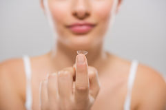 Woman holding contact lens Stock Photo