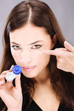 Woman holding contact lenses cases and lens. Young woman holding contact lenses cases and lens in front of her face stock photos