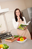 Woman holding cookbook woman in the kitchen Stock Images