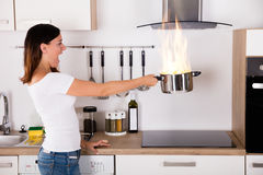 Woman Holding Cooking Pot With Fire. Shocked Young Woman Holding Cooking Pot With Fire Near Modern Gas In Kitchen Royalty Free Stock Photography