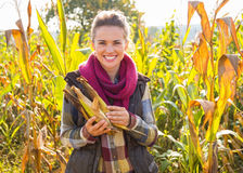 Woman holding corn while standing in cornfield Royalty Free Stock Image