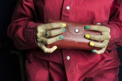 Woman Holding Cosmetic Case. Woman wearing red shirt holding a cosmetic case, studio cropped shot Stock Photo