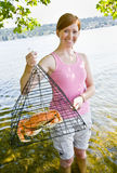 Woman holding crab in trap Royalty Free Stock Photos