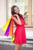 Woman holding credit card and bags Stock Photos