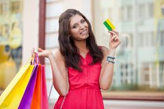 Woman holding credit card and bags Royalty Free Stock Photo