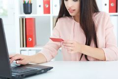 Young woman holding credit card in hand and entering security code using laptop keyboard. Woman holding credit card in hand and entering security code using stock images