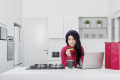 Woman holding credit card in kitchen Royalty Free Stock Photos