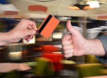 Woman holding credit card, man gesturing thumb up Royalty Free Stock Photography