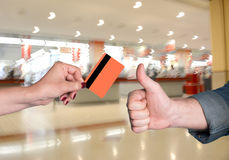 Woman holding credit card, man gesturing thumb up Royalty Free Stock Photo