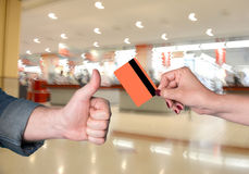 Woman holding credit card, man gesturing thumb up Stock Images