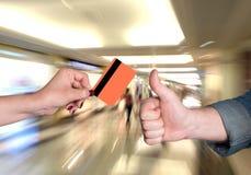 Woman holding credit card, man gesturing thumb up Stock Photo