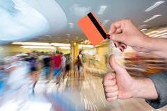Woman holding credit card, man gesturing thumb up Royalty Free Stock Photo