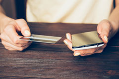 Woman holding a credit card and mobile phone Royalty Free Stock Image