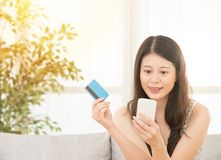 Woman holding credit card online shopping. Close up happy woman hands holding credit card and using mobile smart phone Online shopping, Asian Caucasian model Royalty Free Stock Photos