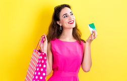 Woman holding a credit card and a shopping bag Royalty Free Stock Photography
