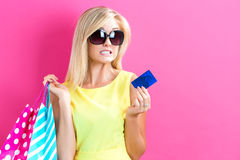 Woman holding a credit card and shopping bags Stock Images