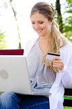 Woman holding credit card and smiling Royalty Free Stock Photo