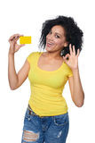 Woman holding credit card. Smiling mixed race african american caucasian woman holding credit card and gesturing OK, isolated on white background Royalty Free Stock Photos