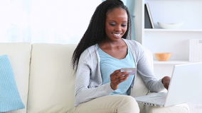Woman holding a credit card while typing on a laptop stock footage