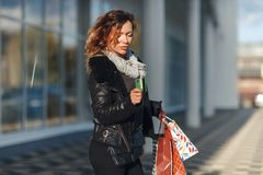Woman holding a credit card and using cell phone for online shopping royalty free stock photo