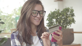Woman holding a credit card and using cell phone for online shopping Royalty Free Stock Photography