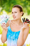 Woman holding credit cards and cash Stock Image