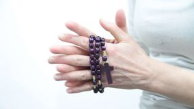 Woman holding a cross with beads in her hands stock footage