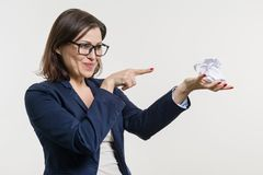 Woman holding a crumpled paper ball in her hand, with her finger down on the ball. stock photos