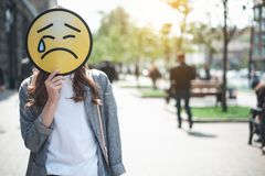 Woman is holding crying face sign outdoors. Lady is standing in the street and hiding face behind upset emoticon with falling tear. Sadness concert. Copy space stock image