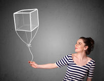 Woman holding a cube balloon. Pretty young woman holding a drawn cube balloon Royalty Free Stock Image