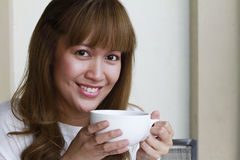 Woman Holding Cup. A young attractive woman drinking coffee or tea. (Shallow depth of field with focus on the model's eyes Royalty Free Stock Images