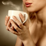 Woman holding cup and blowing on it Royalty Free Stock Images