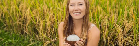 A woman is holding a cup of boiled rice in a wooden cup on the background of a ripe rice field BANNER, LONG FORMAT stock image
