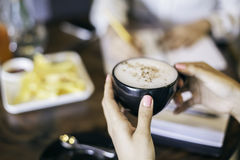 Woman holding a cup of cappuccino Stock Photo