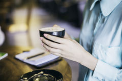 Woman holding a cup of cappuccino Royalty Free Stock Photo