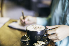Woman holding a cup of cappuccino Stock Photos