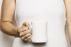 Woman Holding Cup of Coffee. A woman holds a cup of coffee in her right hand Royalty Free Stock Photography